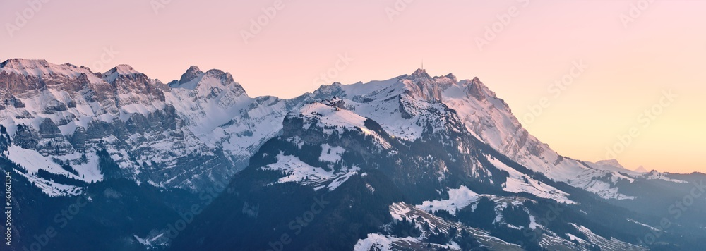 Fototapeta Beautiful scenery of a range of high rocky mountains covered with snow at sunset