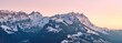 Beautiful scenery of a range of high rocky mountains covered with snow at sunset