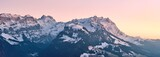 Fototapeta Fototapety na ścianę - Beautiful scenery of a range of high rocky mountains covered with snow at sunset