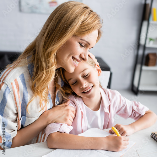 Fototapeta Smiling mother embracing kid writing on notebook at table obraz