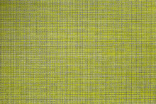 The Table Mat Is Yellow, Woven From Thin Plastic Rods.