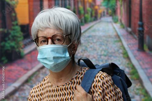 Fototapeta Senior woman wearing a mask outdoors to flatten the curve  obraz