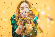 Portrait Of Woman Blowing Confetti Against Yellow Background