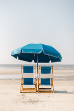 Two Blue Beach Chairs And Umbr...