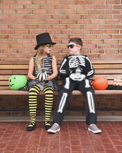 Children Wearing Halloween Costumes On Bench