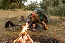 The Blond Girl In The Autumn Outfit Sits Near The Firebond In The Chair At The Camp Enjoying The Atmoshere