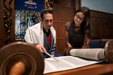 Synagogue: Rabbi Practicing Torah Reading With Teen Girl