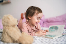 Adorable Toddler Girl Lying On Bed Watching Book