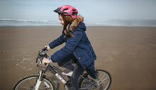 Family Bike Ride On The Sand At Cannon Beach, Oregon.