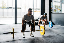 Men Exercising With Barbells In A Crossfit Box