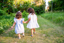 Two Young Girls Holding Hands Walking Outdoors