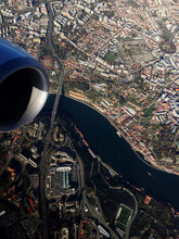 High Angle View Of Airplane Flying Over Buildings In City
