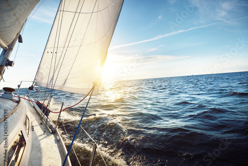 White sailboat in an open sea at sunset Fototapete