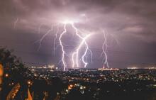 Lightning Over Illuminated Cityscape Against Sky At Night