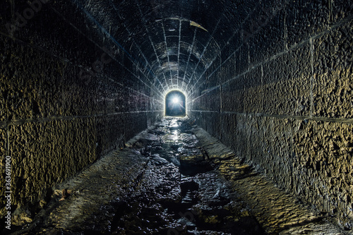 Dark and creepy old historical vaulted flooded underground drainage tunnel Canvas