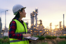 Asian Woman Petrochemical Engineer Working At Night With Laptop Inside Oil And Gas Refinery Plant Industry Factory At Night For Inspector Safety Quality Control..