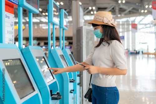 Asian woman traverler wearing mask using self check-in kiosk in airport terminal during coronavirus (COVID-19) pandemic prevention when travel abroad Canvas Print