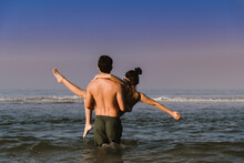 Rear View Of Shirtless Man Carrying Woman While Standing In Sea