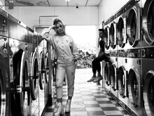 Full Length Portrait Of Young Woman Standing By Washing Machines