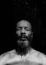 Shirtless Man Taking Shower Against Black Background