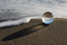 Crystal Ball On Beach By Water With Sea Foam.