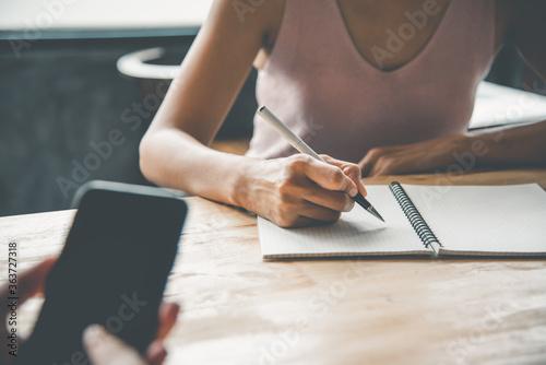 Fototapeta Closeup of woman's hand writing on paper obraz na płótnie