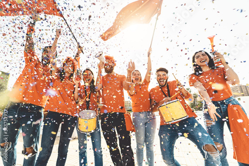 Fotografiet Low Angle View Of Happy Fans Enjoying On Street