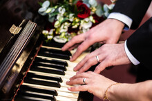 Cropped Hands Of Couple Playing Piano