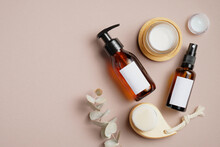 Cosmetics SPA Branding Mockup. Dark Amber Glass Pump Bottle Dispenser And Spray, Facial Cleaning Brush, Natural Organic Body Cream And Eucalyptus Leaves On Beige Background. Flat Lay, Top View.
