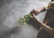 花を握る老齢の女性の...