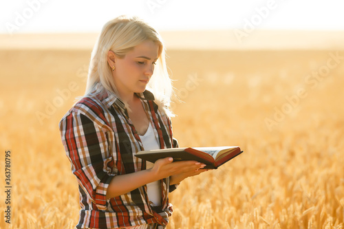 Christian woman praying on holy bible and wooden cross in barley field on summer Wallpaper Mural