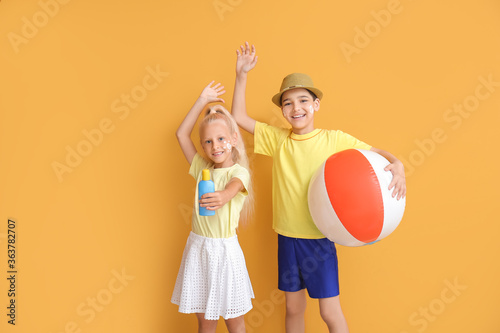 Fototapeta Little children with sun protection cream and inflatable ball on color background obraz
