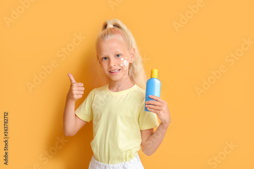 Fototapeta Little girl with sun protection cream showing thumb-up gesture on color background obraz