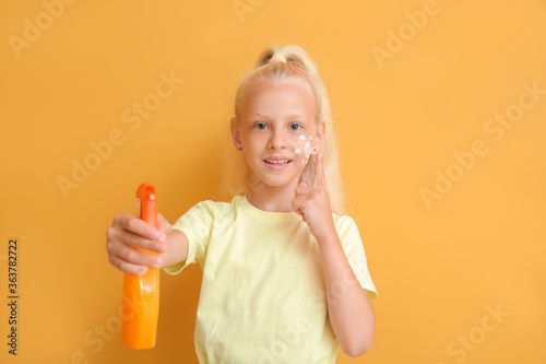 Fototapeta Little girl with sun protection cream on color background obraz