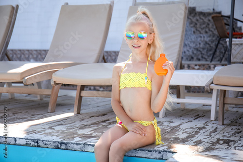 Fototapeta Little girl with sun protection cream near swimming pool obraz