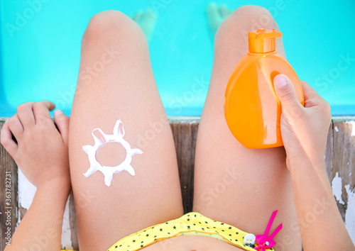Fototapeta Little girl with sun protection cream near swimming pool, top view obraz