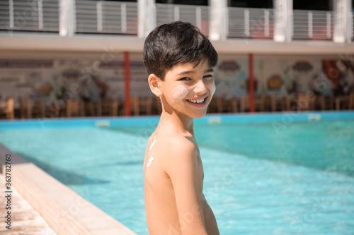 Fototapeta Little boy with sun protection cream on his body near swimming pool obraz