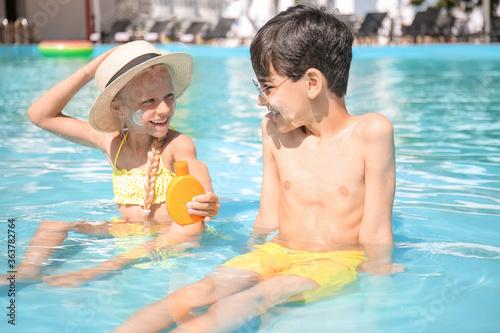 Fototapeta Little children with sun protection cream in swimming pool obraz