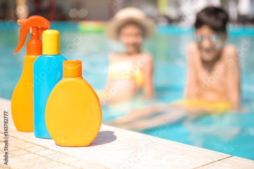 Fototapeta Bottles of sun protection cream near swimming pool obraz