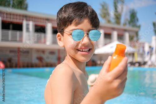 Fototapeta Little boy with sun protection cream near swimming pool obraz