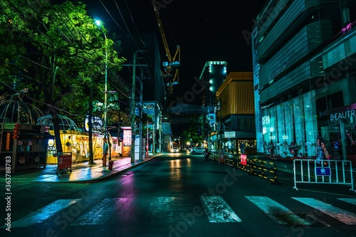 Fototapeta Illuminated City Street And Buildings At Night obraz na płótnie