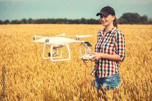 Fototapeta agronomist woman walking on field with drone flying above farmland at sunset obraz