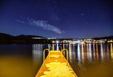 Illuminated Pier Over Lake Against Sky At Night