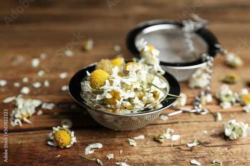 Fényképezés Dry chamomile flowers in infuser on wooden table, closeup