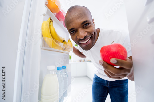 Close-up portrait of his he nice attractive cheerful cheery guy looking in fridge taking red ripe apple snack health care lifestyle regime in light white interior house kitchen indoors