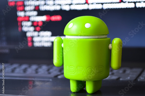 Photo A green android figure stands on a laptop on a programming code screen
