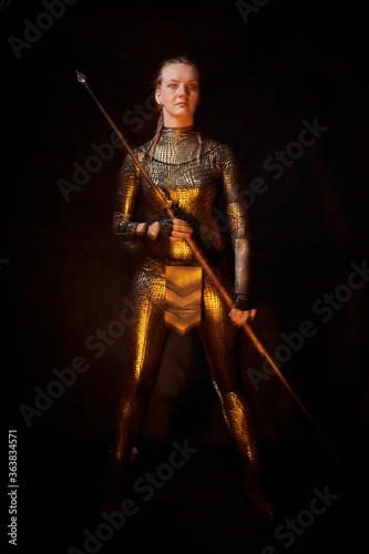 Valkyrie girl in shiny military armor and with a spear in a dark room with plants and vines Wallpaper Mural
