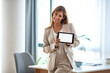 canvas print picture - Shot of a young businesswoman holding up a digital tablet with a white screen in an office. Businesswoman With Digital Tablet By Window Of New Office.