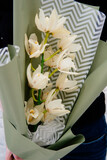Bouquet of orchid flowers in pistachio-colored package