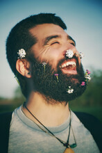 Close-up Of Happy Man With Flowers On Face